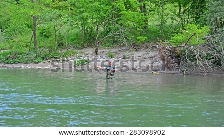 A man casting a fly, while fly-fishing in waist deep water  - stock photo