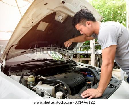 A man checking car engine at home - stock photo