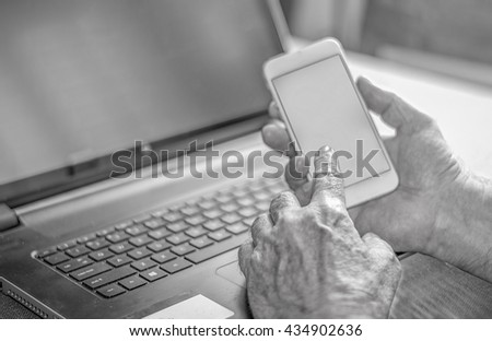 a man checking on his phone in front of a notebook
