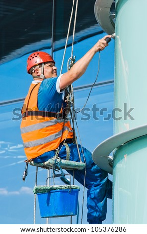 A man cleaning windows on a high rise building - stock photo