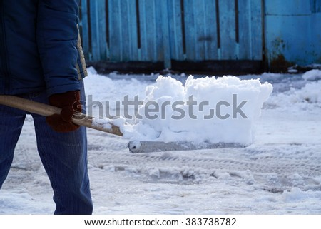 a man cleans snow shovel in the yard - stock photo