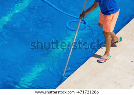 A man cleans the swimming pool with a net. Summer maintenance service