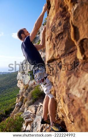 A man climbing a very steep mountain  -Rock Climbing - stock photo