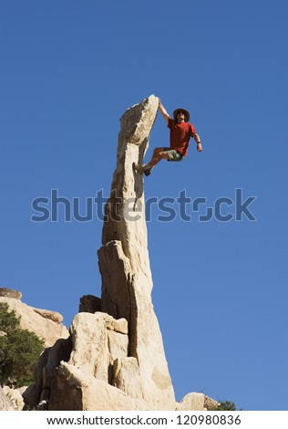 a man climbing up a steep narrow rock spire