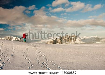 A man climbs on a snow slope - stock photo