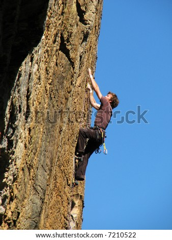 a man climbs up an overhanging rock face