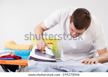 A man concentrated on ironing a shirt - stock photo