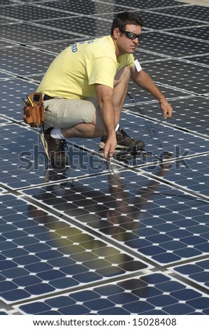 a man connects cables while installing a solar panel - stock photo
