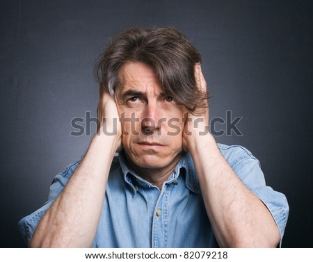 A man covers his ears with his hands. Suffering from a loud sound. - stock photo