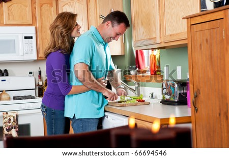 A man cutting vegetables preparing for dinner with his wife - stock photo