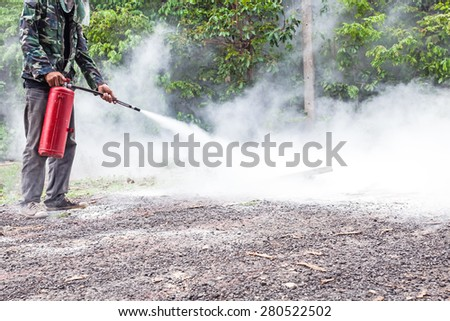A man demonstrating how to use a fire extinguisher - stock photo