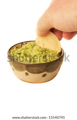 A man dipping a chip in a bowl of guacamole - stock photo