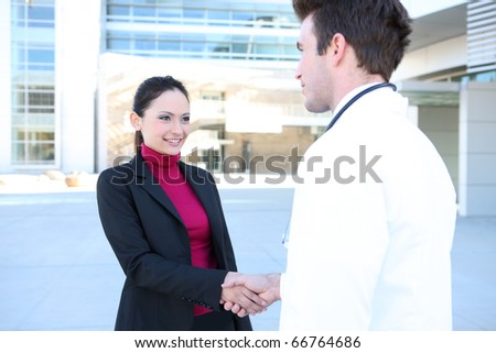 A man doctor and woman patient shaking hands outside hospital