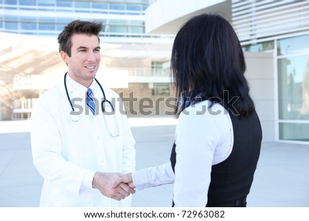 A man doctor and woman patient shaking hands outside hospital - stock photo