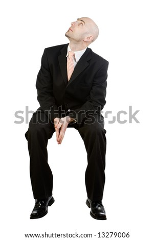 A man dressed in a business suit is sitting in a chair waiting. - stock photo