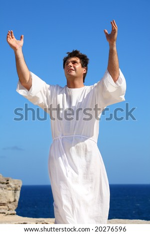 A man dressed in white robe with hands raised in spiritual devotion, praise or happiness. - stock photo