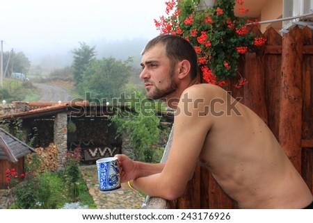 A man drinking tea on the balcony - stock photo