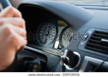 A man driving a car with his hand on the wheel - stock photo