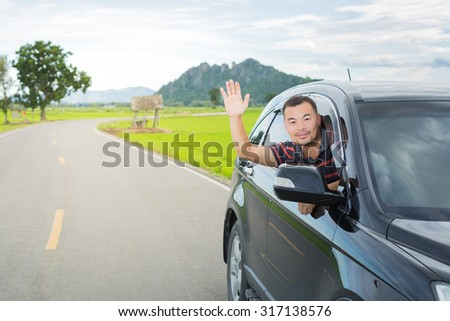A man driving car and show his hand for greet