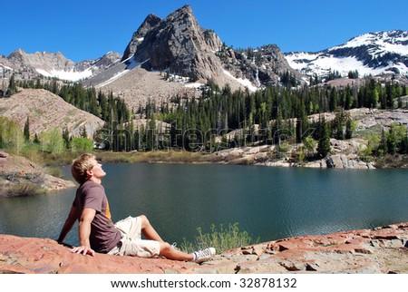 A man enjoying the sun next to a mountain lake. - stock photo