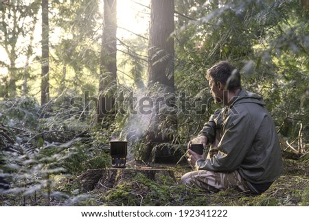 A man enjoys a hot drink in a forest. Cooked on a camping stove. - stock photo