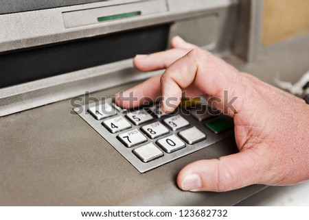 a man enters his pin into the atm. - stock photo