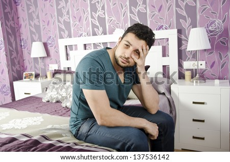 A man exhausted with eye circles in vintage bedroom.