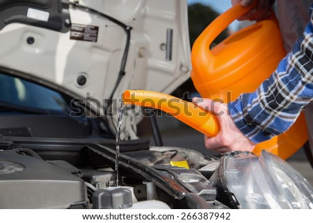 A man fills his car with fresh water with a orange canister. - stock photo