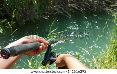 A man fishing with a fishing rod and fish enjoys silence - stock photo