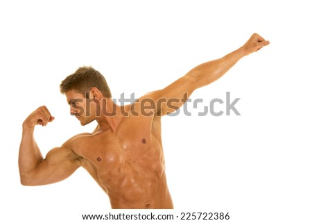 A man flexing his muscles looking down at his bicepts. - stock photo