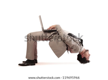 A man gets upside down while using a computer - stock photo