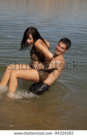 A man getting ready to dunk his woman in the water, the woman is screaming. - stock photo