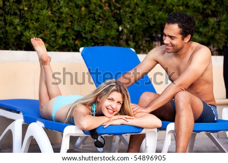 A man giving a back massage to a woman on a beach chair - stock photo
