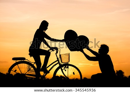 a man giving a big heart to a woman riding a bicycle silhouette