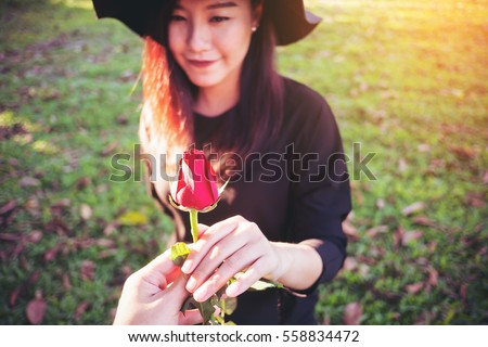 A man giving a red rose flower to asian women on Valentine's day with green grass background