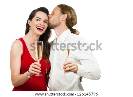 A man giving a woman a kiss on the cheek while having some champagne. Isolated on white. - stock photo
