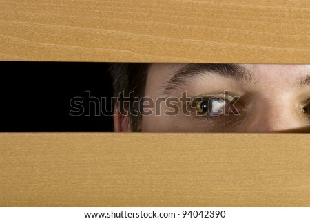 A man glances through the blinds - stock photo