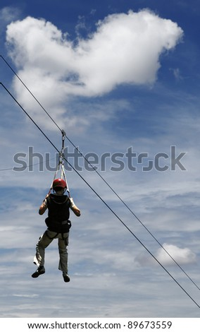 A man gliding on the flying fox contraption against a blue cloudy sky. - stock photo