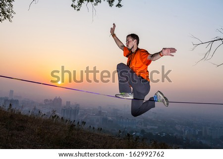 A man goes and shows tricks on the tightrope at the sunset and the city slack-line - stock photo