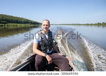 a man goes fishing control  river on a motorboat