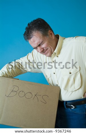 A man grimacing as if with back pain from lifting a box filled with books. - stock photo