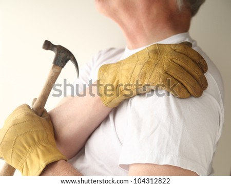 a man grips his shoulder as he tries to do repairs - stock photo