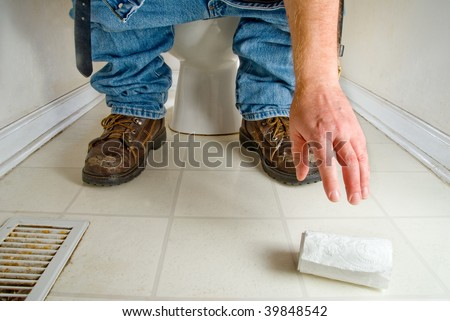 A man gropping for fallen toilet paper.