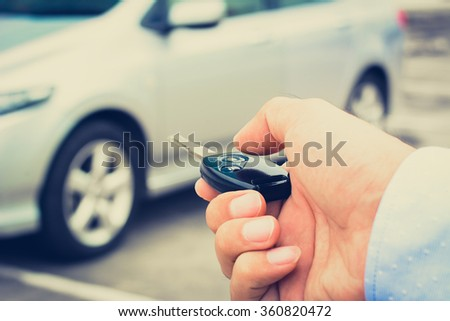 A man hand about to press button of remote control car key, vintage tone - stock photo