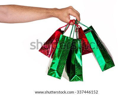 A man hand carrying a bunch of colorful shopping bags - stock photo