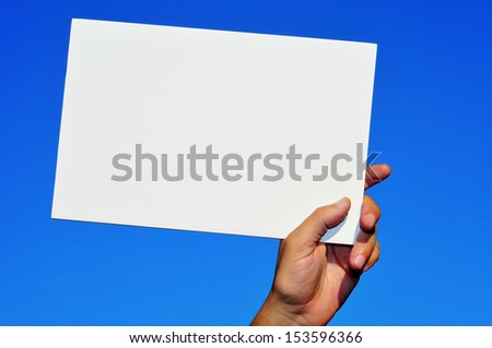 a man hand holding a blank signboard with a copy-space over the blue sky - stock photo