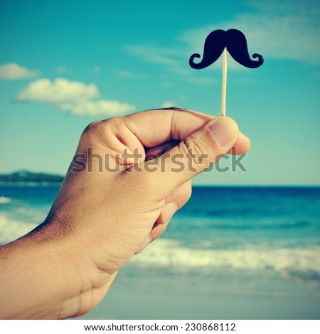 a man hand holding a fake moustache in a stick in his hand on the beach, with a filter effect - stock photo