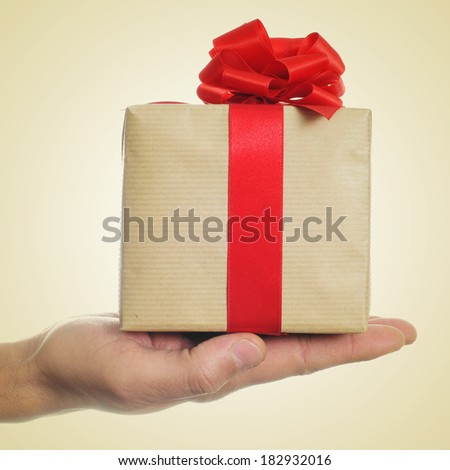 a man hand holding a gift with a red ribbon on a beige background, with a retro effect - stock photo