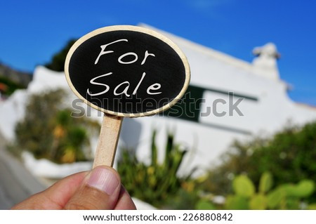 a man hand holding a signboard with the text for sale written in it in front of a house - stock photo