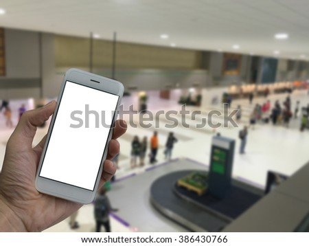 A man hand holding empty screen of smart phone and blur the airport waiting for baggage background. - stock photo